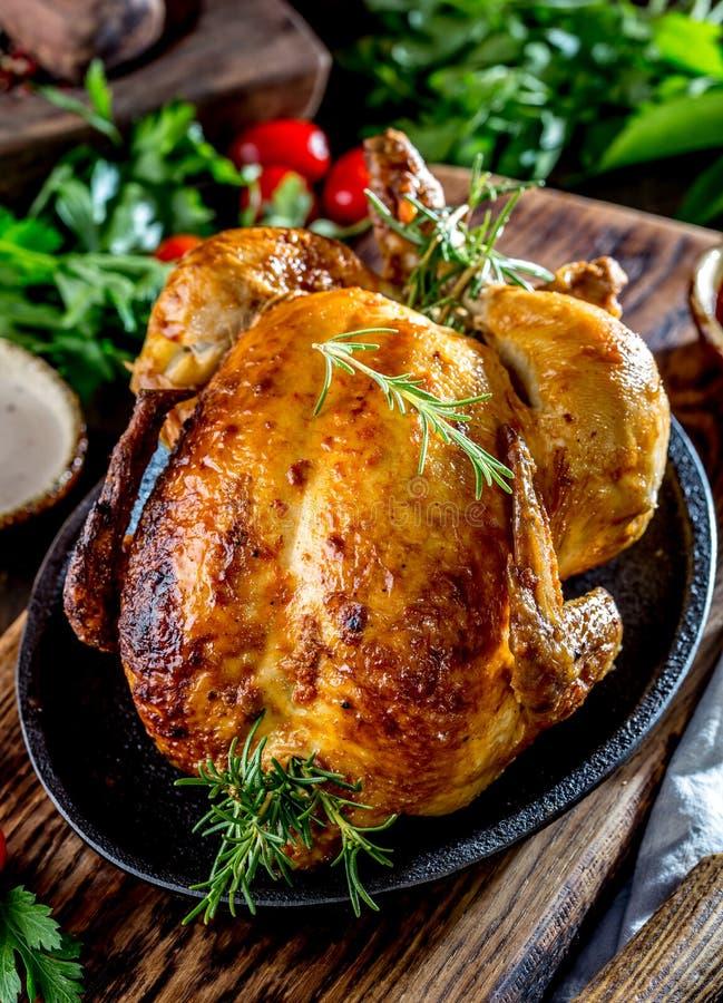Gebratenes Huhn mit Rosmarin diente auf Schwarzblech mit Soßen auf Holztisch, Abschluss oben stockfoto