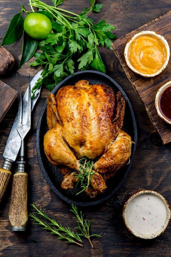 Gebratenes Huhn mit Rosmarin diente auf Schwarzblech mit Soßen auf Holztisch, Draufsicht stockfoto