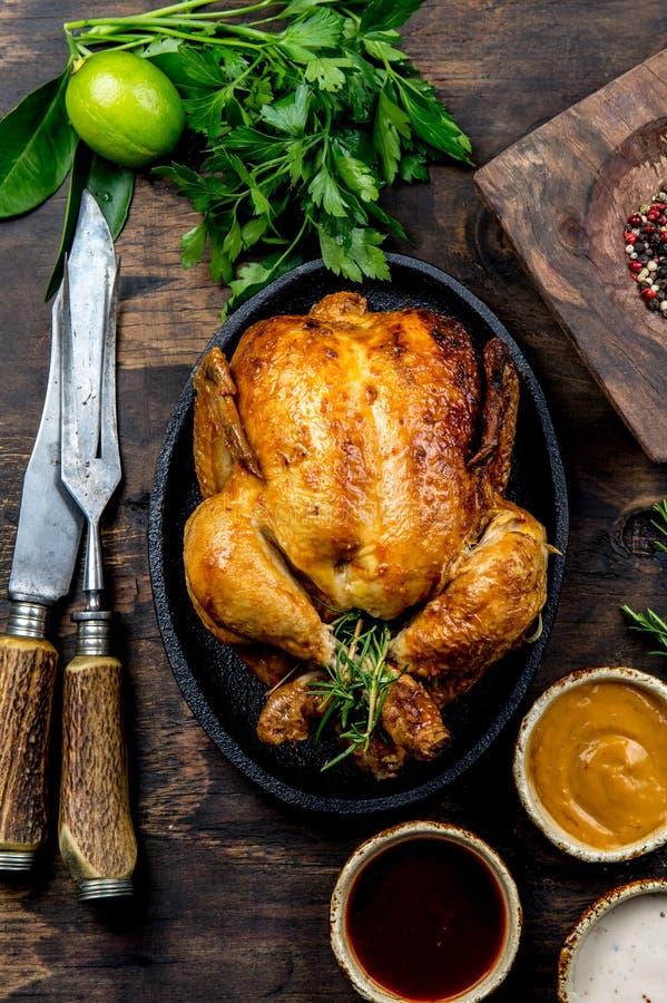 Gebratenes Huhn mit Rosmarin diente auf Schwarzblech mit Soßen auf Holztisch, Draufsicht lizenzfreie stockfotografie