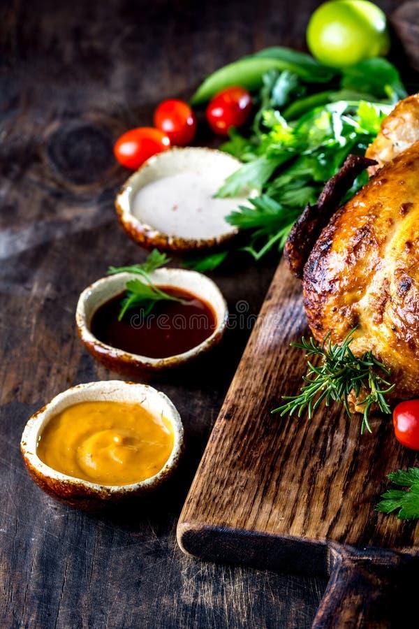 Gebratenes Huhn mit Rosmarin diente auf Schwarzblech mit Soßen auf Holztisch, Draufsicht stockfotografie