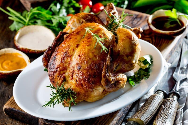 Gebratenes Huhn mit Rosmarin diente auf weißer Platte mit Soßen auf Holztisch, selektiver Fokus lizenzfreie stockfotos