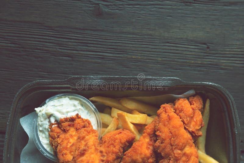 Gebratenes Huhn und Pommes-Frites und in einem Mitnehmerbeh?lter auf dem h?lzernen Hintergrund Nahrungsmittellieferung und Schnel lizenzfreies stockfoto