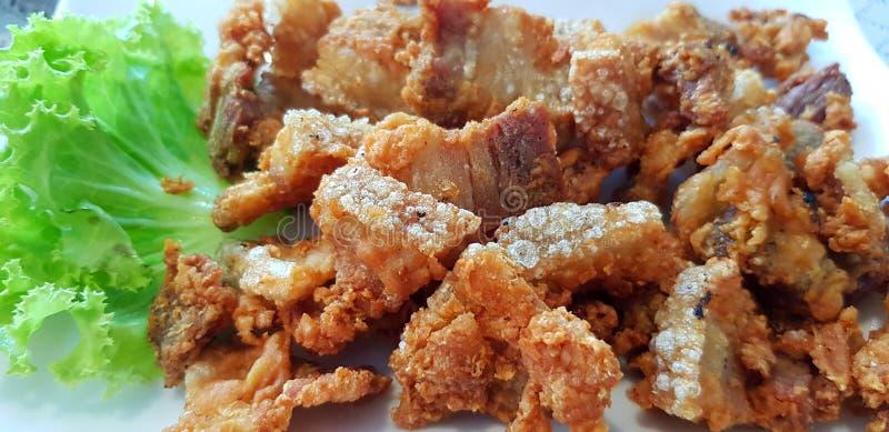 Gebratenes knusperiges Schweinefleisch mit Grünkohlblatt auf weißer Platte am thailändischen Restaurant stockfoto