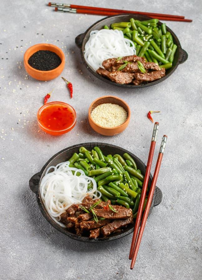 Gebratenes würziges Rindfleisch mit Samen des indischen Sesams, grünen Bohnen und Reisnudeln lizenzfreies stockbild