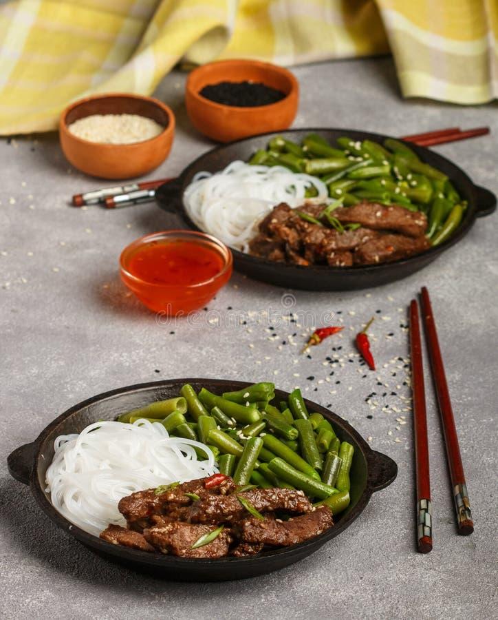 Gebratenes würziges Rindfleisch mit Samen des indischen Sesams, grünen Bohnen und Reisnudeln stockbild
