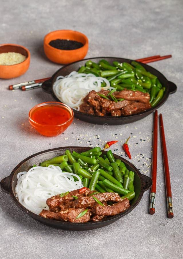 Gebratenes würziges Rindfleisch mit Samen des indischen Sesams, grünen Bohnen und Reisnudeln stockfotografie