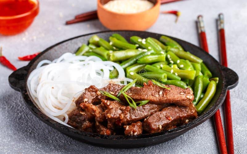 Gebratenes würziges Rindfleisch mit Samen des indischen Sesams, grünen Bohnen und Reisnudeln lizenzfreie stockbilder