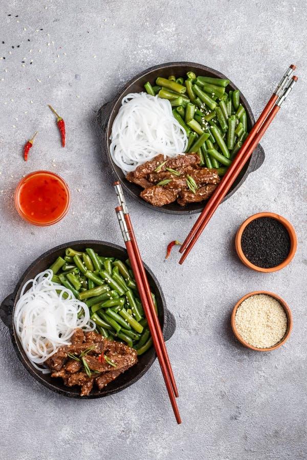 Gebratenes würziges Rindfleisch mit Samen des indischen Sesams, grünen Bohnen und Reisnudeln stockfoto