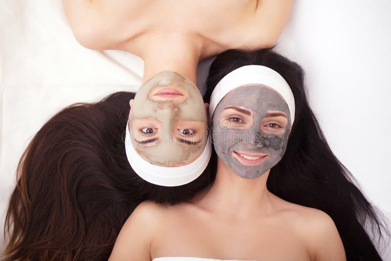 Gebrauch von einer Gesichtsmaske zu den jungen Frauen des Gesichtes zwei in einem Schönheitssalon stockfoto
