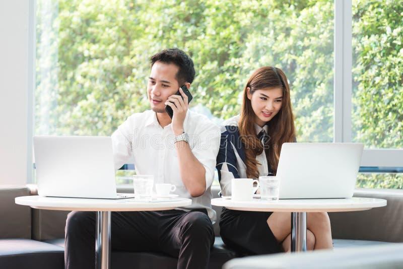 Gebrauchs-Laptoparbeit mit zwei asiatische Mitarbeitern zusammen stockfotos