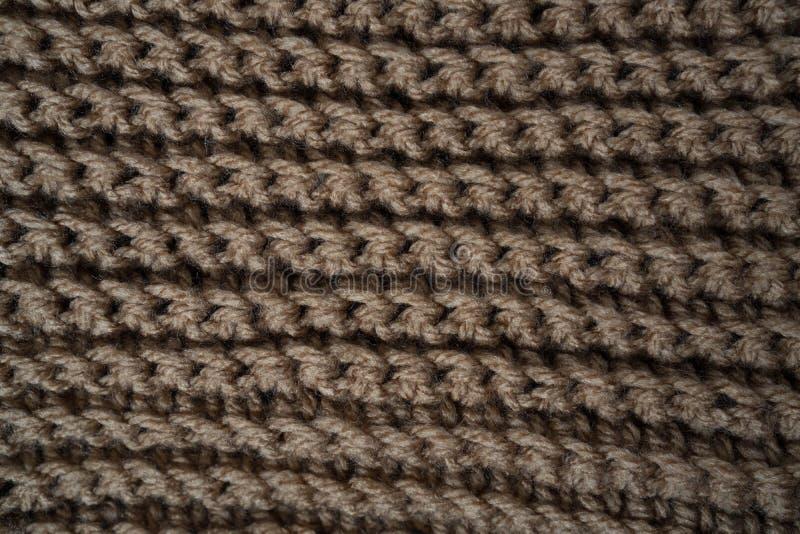 Gebreide horizontale geweven bruine stof op een witte achtergrond Fragment van een bruine kleurensweater De textuur, sluit omhoog stock foto