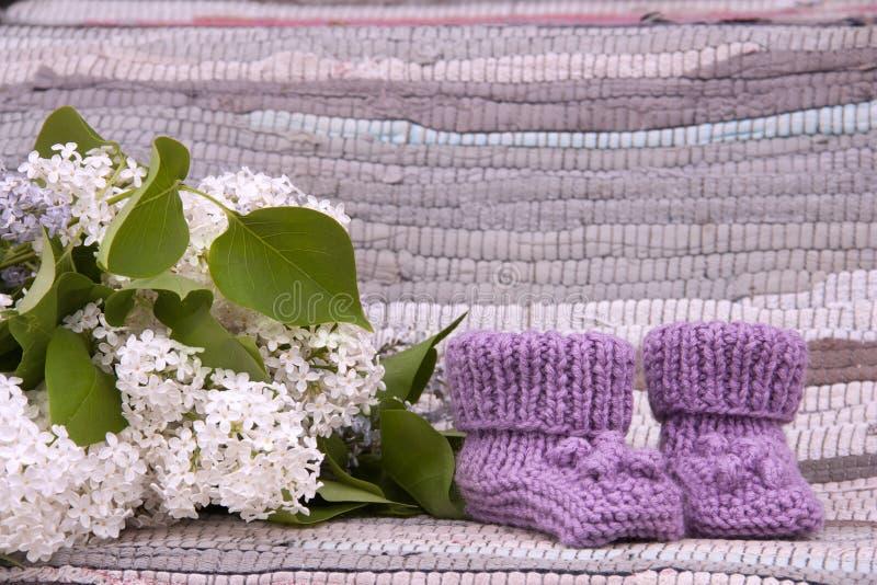 Gebreide lilac babybuiten op landelijke achtergrond royalty-vrije stock foto