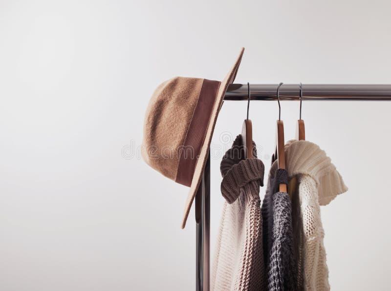 Gebreide sweaters op hangers en vilten hoed stock afbeelding