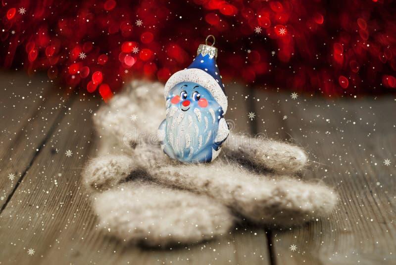 Gebreide vuisthandschoenen en Kerstmisdecoratie op houten achtergrond stock afbeeldingen