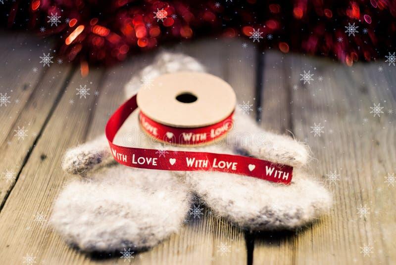 Gebreide vuisthandschoenen met lintdecoratie met liefde op houten backg stock foto's
