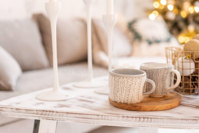 Gebreide wollen koppen op een houten lijst Twee koppen van hete koffie het concept hitte Vakantie en gebeurtenissen De herfst en stock afbeelding