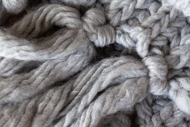 Gebreide wollen sjaal met leeswijzers, macro Zachte grijze merinoswolachtergrond, close-up De herfst en de wintervlakte lag stock afbeelding