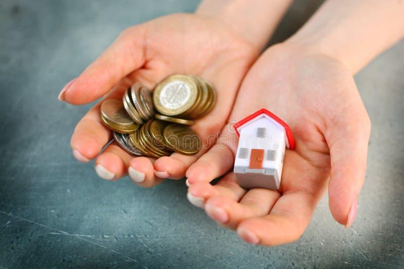 Gebrek aan geld om een huisconcept te kopen De vrouw houdt stuk speelgoed huis in één hand en handvol muntstukken in een andere stock fotografie