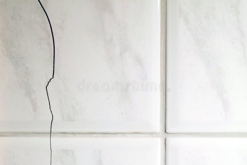 Gebrochene Fliesen auf der Badezimmerwand stockbilder