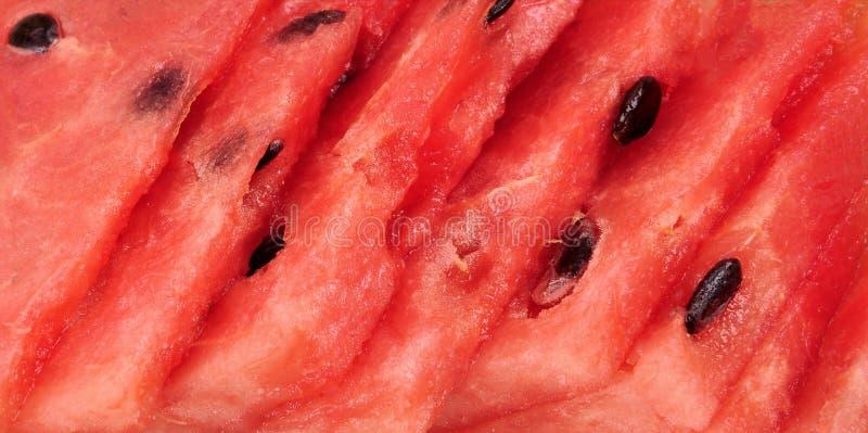 Gebrochene geschnittene Stücke der Wassermelone masern roten Hintergrund Abschluss oben lizenzfreie stockfotos