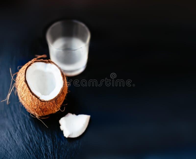 Gebrochene Kokosnuss mit Kokosmilch in einem Glas Coconuß geschnitten in h lizenzfreie stockfotos
