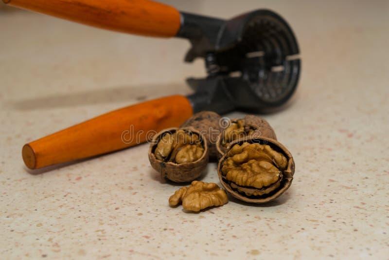 Gebrochene wallnuts mit Nusscracker im Hintergrund stockfotos