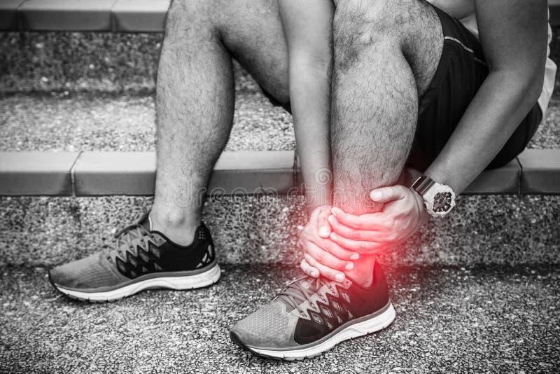 Gebrochener verdrehter Kn?chel Läufer, der Fuß in den Schmerz wegen des verstauchten Knöchels berührt stockfotos