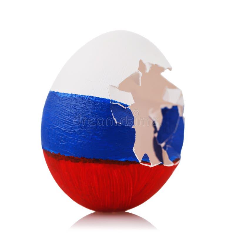 Gebrochenes Ei gemalt in der Farbe der russischen Flagge auf weißem Hintergrund Konzept bezüglich des Schlages zur Orthodoxie lizenzfreie stockbilder