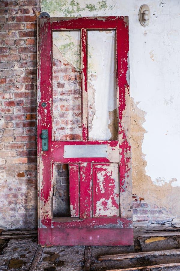 Gebroken deur en bakstenen muur stock fotografie