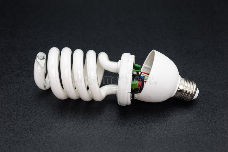 Gebroken die energie - besparings gloeilamp, op een zwarte achtergrond met een het knippen weg wordt geïsoleerd royalty-vrije stock foto
