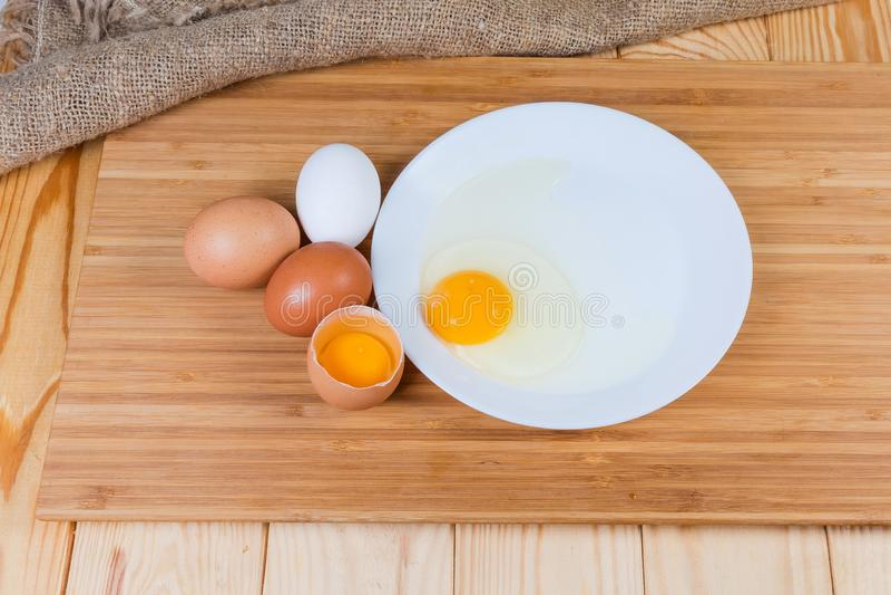 Gebroken en gehele eieren op scherpe raad op rustieke lijst royalty-vrije stock fotografie