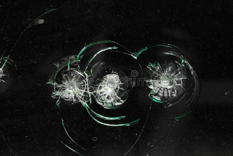 Gebroken gebarsten glas met gat over zwarte achtergrond stock afbeelding