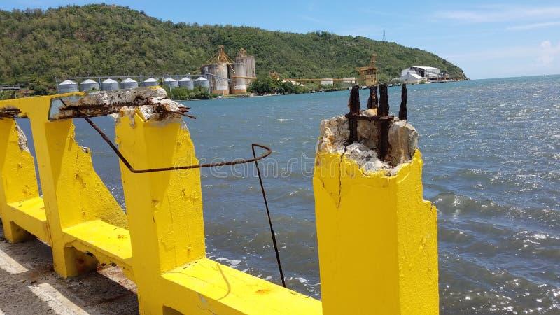 Gebroken geel cement met rebar en zeewater in Guanica, Puerto Rico stock fotografie