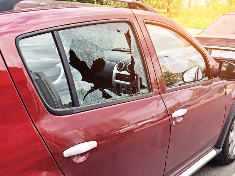 Gebroken glas op de passagiersdeur van een geparkeerde personenauto Het concept misdaad van autodiefstal, diefstal van kostbaarhe royalty-vrije stock foto