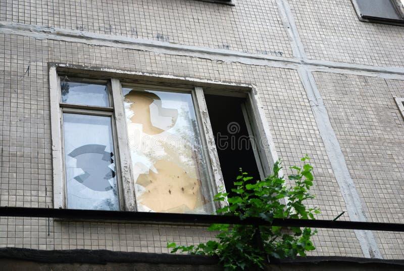 Gebroken glazen venster in verlaten die huis met triplex wordt belemmerd royalty-vrije stock afbeelding