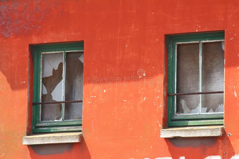 Gebroken groene houten vensters voor vernieuwing, om op oranje voorgevel te verkopen stock afbeeldingen