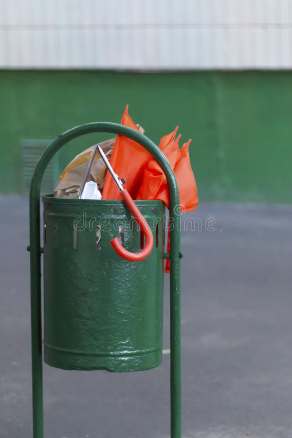 Gebroken heldere oranje paraplu in groene vuilnisbak royalty-vrije stock fotografie