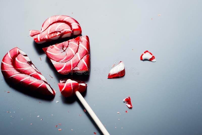 Gebroken lolly in vorm van hart op een donkere achtergrond met exemplaarruimte stock fotografie