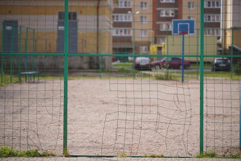 Gebroken netwerk van metaalomheining van een basketbalhof stock afbeelding