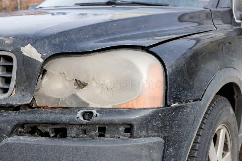 Gebroken per toeval voorkoplamp op een zwarte auto, wielachtergrond Het herstellen van Concept stock foto