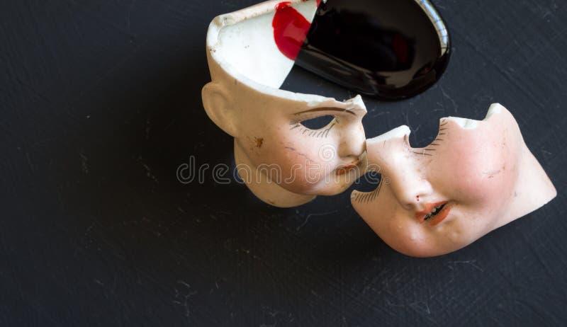 Gebroken poppengezichten en bloed op grunge zwarte achtergrond stock afbeelding