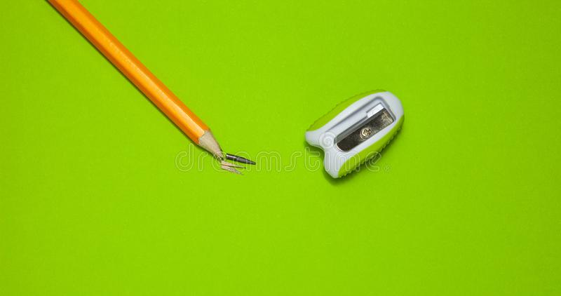 Gebroken potlood en slijper op groene achtergrond, hoogste mening royalty-vrije stock fotografie