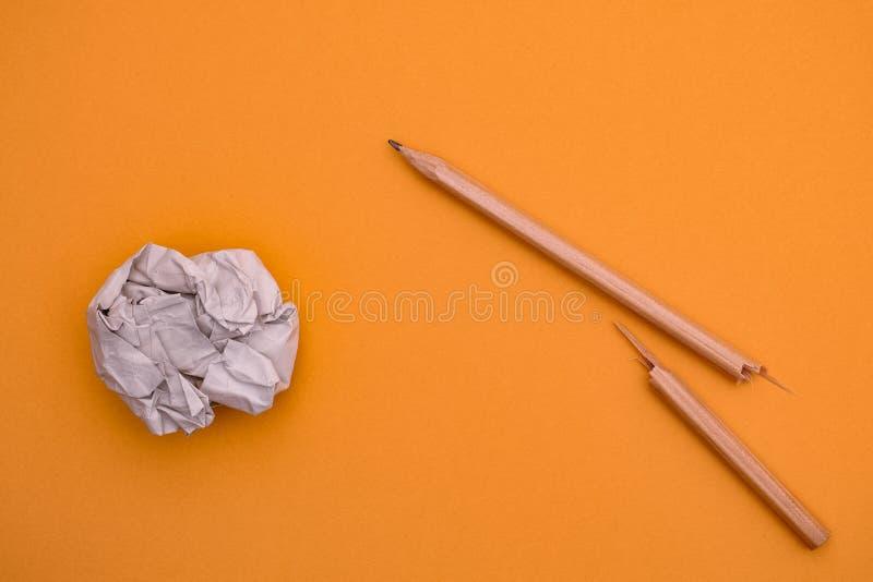 Gebroken potlood en verfrommelde document bal op een gele achtergrond royalty-vrije stock afbeeldingen