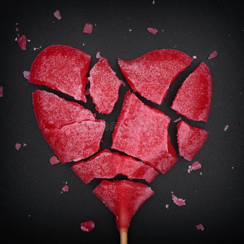Gebroken rode hart gevormde lolly stock afbeeldingen