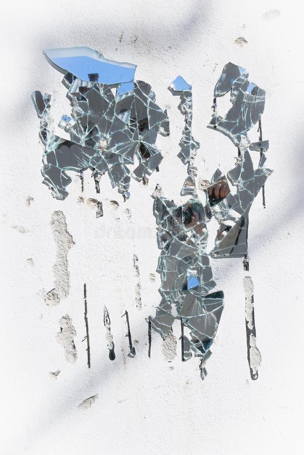 Gebroken spiegel op witte oude muur stock foto