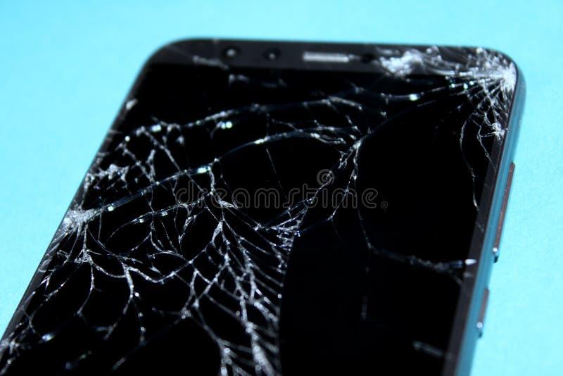 Gebroken telefoon op blauwe achtergrond Het gebarsten scherm stock foto
