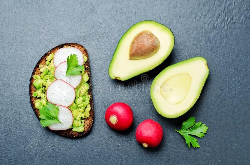 Gebroken van de de peterselierogge van de avocadoradijs het ontbijtsandwich stock foto's