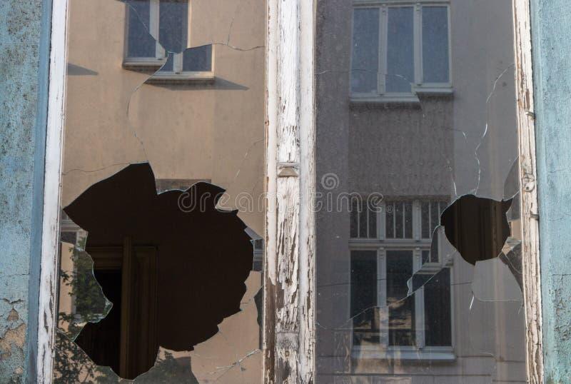 Gebroken vensterglas in de verlaten oude bouw Vuile voorgevel Hamer op verbrijzeld glas met splinters Vandalismeconcept De buiten stock fotografie
