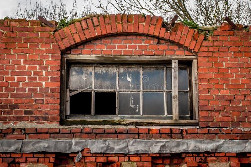 Gebroken vensters in een oud gebouw met gebroken bakstenen stock afbeelding