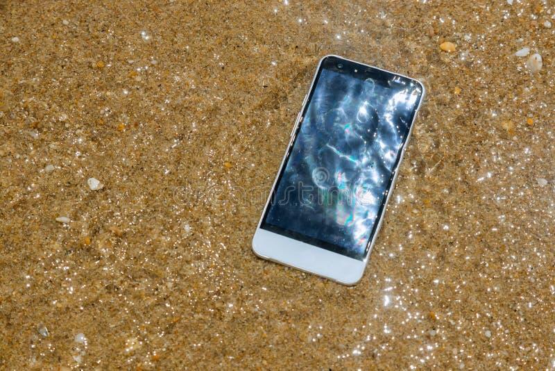 Gebroken verpletterde smartphone ligt in het water Telefoon in het zandige strand stock foto
